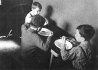Evžen Adámek na fotografii vpravo v dětských letech při nedělním obědě s bratry Josefem a Stanislavem