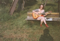 Iveta, aged 17, dutifully practices guitar in the garden.