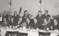 """A rare photograph of one of the airline employee parties. Jan is in the centre, partly hidden behind a vase of flowers. At that time, nobody was really aware of the dangers of the upcoming political changes which were, so far only inconspicuously, peeking at them from the sign behind their backs. One says, in Slovak, """"More flour and bread for the state - further steps towards socialism"""""""