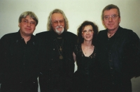 A reminder of an anniversary concert of the Taxmen band. The photograph was taken at a party which took place in Mánes [gallery] probably at an anniversary of starting the Taxmen band; other artists participated as well. On the left, founder of Taxmen and a wonderful historian, Jaroušek Čvančara. Iveta as a co-organiser of the event added a bonus for the band members, she invited an astrologer, dr. Peter Messany, to foretell them further career. Far right, on Iveta's left, there is another long term member of the band, owner of a mesmerising baritone, Vráťa Vyskočil. (This was in 2002 or 2003).