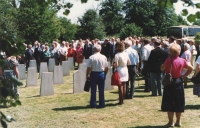 And here we have another photograph from the memorial book shows the memorial service at the graves of the Czechoslovak airmen. The quality of the photograph shot on foreign-made film is apparent at the first sight compared with Ivana's shots. Well, this was Kodak and at that time, the Czechoslovaks were happy if they managed to get, through friends of friends, the East German, socialist, Orwo brand. Even in this year, in 1990. Iveta is well visible on the photograph, with her back towards the viewer, dressed in white.