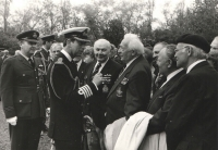 """Another beautiful snapshot from a memorial ceremony at the Olšany cemetery. Behind Prince of Wales's back, a part of Jiří Maňák's face is showing, Jan Irving is smiling at one of his best friends, """"tough guy"""" Bohumil Jaroš aka """"Suchar"""" [~dry wit], at whose left, with a coat over his hands, colonel Malý is standing; on his right, wearing a beret, colonel Petr Uruba. Along with Zdeněk Škarvada, Vilda Bufka and others, they were imprisoned at the Sagan camp and later, they were moved to the famous German castle where officers were imprisoned, Coldwitz, and they shared the cells there."""