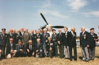 """A beautiful group photo from the very first Memorial Air Show in Roudnice nad Labem on the 23th September, 1991. It was a wonderful event for our airmen and the founder and airport director, Vlasta Dvořák, put his heart into organising this event not only that year but for many years after. The event got called """"Second Britain"""", even. The truth is, for the air fans, the event is made rarer by happening only every other year. Iveta cannot remember all the names after so many years. After the parked Hurricane from The Netherlands, she recognised her dad (second from right) and his colleague from the B-24, Ivan Schwarz (United Kingdom), at her dad's right, colonel Petr (United Kingdom), further from him, Viktor Kent (United Kingdom), colonel Antonín Vendl, and in the RAF uniform, colonel Dvorský. In the centre under the propeller, colonel František Fajtl with his indispensable goatee. From the left, Iveta can identify colonel Krézek (second from left), colonel J. Hofrichter (fourth from left), in grey suit next to him, another pilot legend, colonel Karel Šeda. From those sitting, she can recall colonel J. Vyhnis (who was born in Stod) and fourth from left, František Knap."""