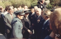 """Olšany cemetery again, the RAF section during the 1992 official visit of U. K. Prime Minister, Margaret Thatcher. She is being escorted by Alois Konopický in a historical RAF uniform, representing the Czechoslovak airmen, and the Prime Minister, who had just greeted colonel Irving, is going to shake the hand of his friend Arnošt Polák, who is standing next to col. Irving. Allegedly, he whispered to Jan: """"Bite it, I've been living in the United Kingdom for more than fifty years, with Margaret almost behind my back, and to shake her hand, I had to come to Prague!"""" One does not need to add that they both burst out laughing."""