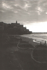 Sunset at a beach in Jaffa with an ancient Christian shrine and fortress on a stony outcrop dominating the landscape