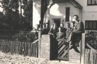 """Photograph of the Czechoslovak pilots taken on the 19th April, 1941, in front of the consular villa """"Praha: left, P. Hlinovský, employee o the consulate, J. Zdráhal, K. Zeman, O. Žanta, J. Grič, J. Irving, by the gate, the Ambasador's daughter, Stela Linhartová (maried Haisová), third from right, Al. Keda, J. Němeček and A. Sedláček"""