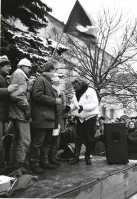 Monika Brázdová na fotografii druhá zprava vystupuje na pódiu s dalšími studenty na demonstraci na Horním náměstí v Humpolci v den generální stávky 27. listopadu 1989