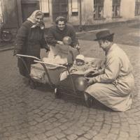Stanislav Duchek v sesličce, v hlubokém kočárku jeho sestra. Zleva babička, maminka a tatínek.