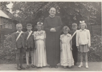 The witness right next to the priest around 1952