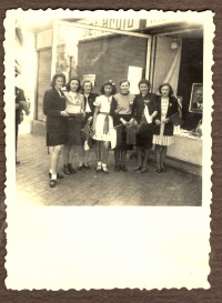 Jaroslava Suchá (in the middle) after the liberation in 1945. The family is standing in front of their house, they are carrying Soviet flags made my Jaroslava´s mother; in the shop window there is a portrait of president Edvard Beneš