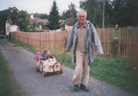 Jaromír Juna with his grandchildren in a home-made toy car