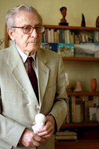 Pavel Oliva with Aristoteles bust in front of a bookshelf with souvenirs (2011)