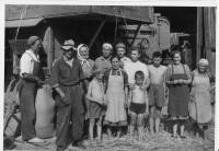 Family with farm hands at the estate, by the thresher - around 1947 (Zbyněk Bezděk is first from the left)