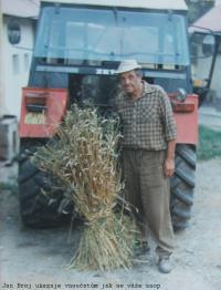 Jan Broj s traktorem ukazuje vnoučatům jak se váže snop