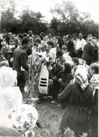 Bishop Pavlo Wasylyk gives the Holy Communion to believers in time of the Divine Liturgy to commemorate the Millennium of Rus'-Ukraine's Baptism. Zarvanytsia, 1988.