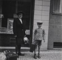 červen 1944 (při odjezdu na Moravu), Libeň, pamětník se služebnou Marií před domem, ve kterém s rodinou bydlel, v ulici U Libeňského pivovaru 1835/19