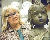 Sculptor Marie Uchytilová, Jiří Hampl's wife, with one of the statues