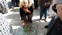 Nora Strejilevich in front of a paving stone carrying the name of her cousin Hugo Daniel Strejilevich and others that were captured at Gutierrez hospital and disappeared (2016)